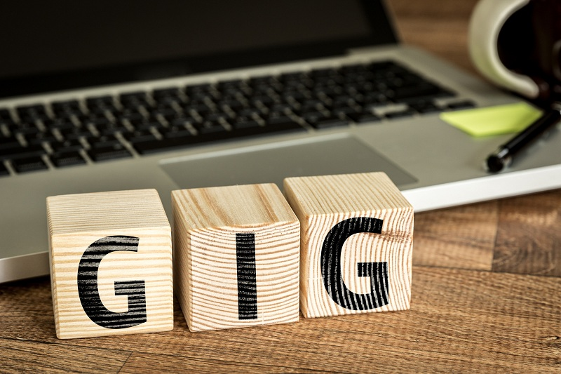 GIG written on a wooden cube in front of a laptop